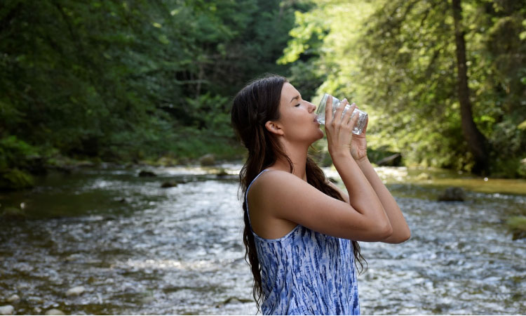 woman drinking water at the river to keep her saliva protecting her teeth