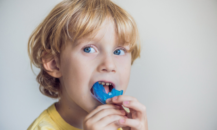 young blond blue eyed boy putting in a mouthguard to protect his teeth