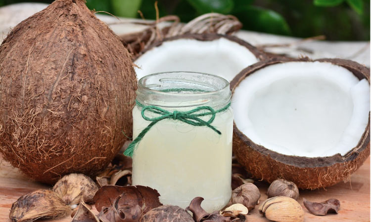 coconuts on each side of a jar of coconut oil