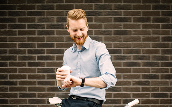 smiling man holding a coffee and looking at his watch