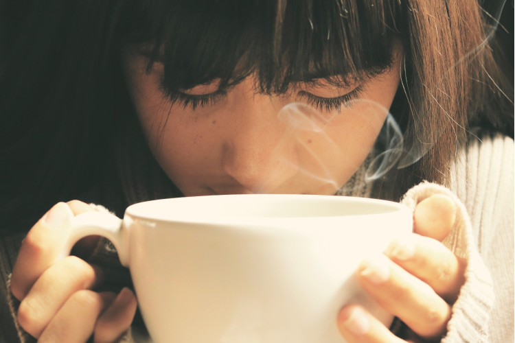 woman drinking from a steaming cup of coffee