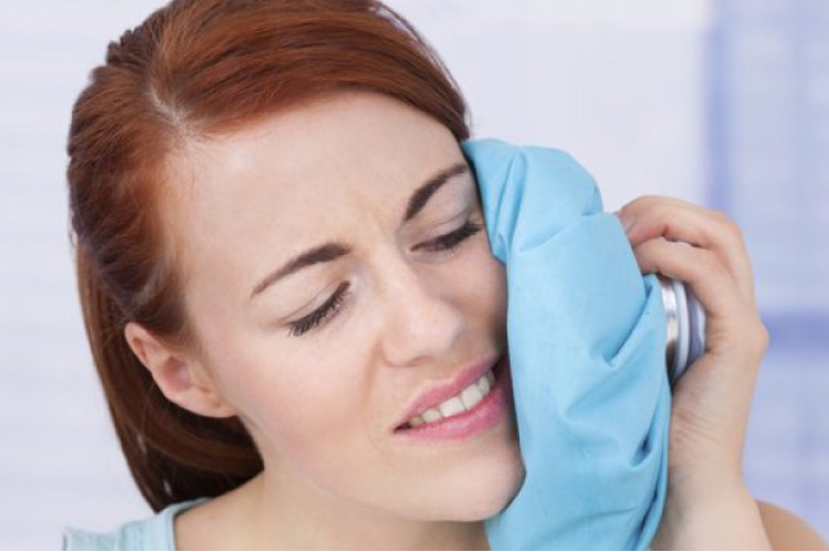 red headed woman applying an ice pack to her jaw after oral surgery