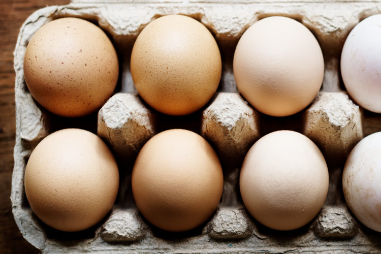 Aerial view of a cardboard carton of uncracked eggs