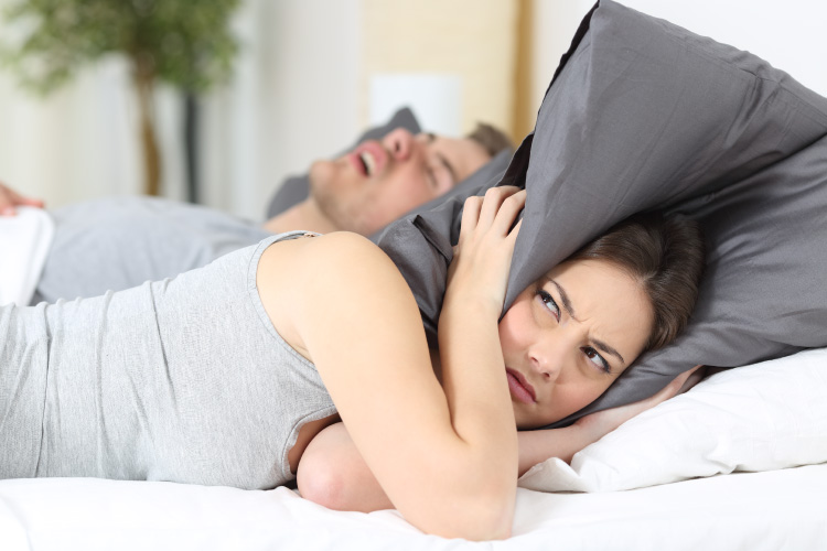 Brunette woman covers her ears with her pillow in frustration due to her snoring husband with sleep apnea