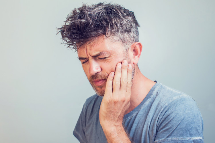 man with messy salt and pepper hair holding his jaw in pain after a dental emergency