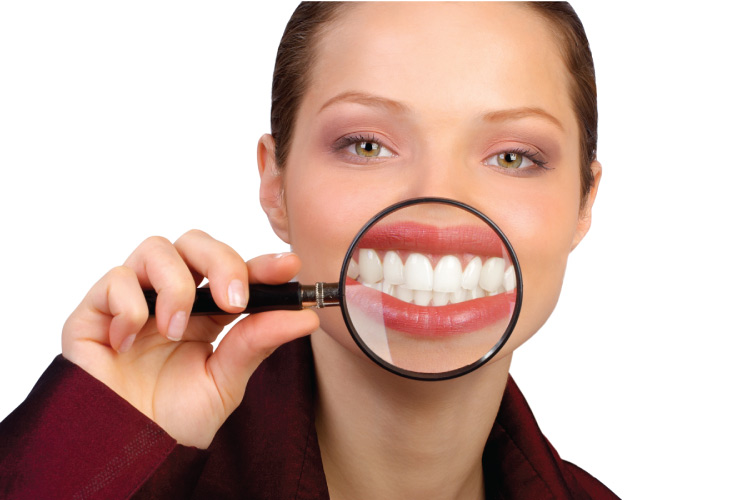 woman holding a magnifying glass in front of her white smile