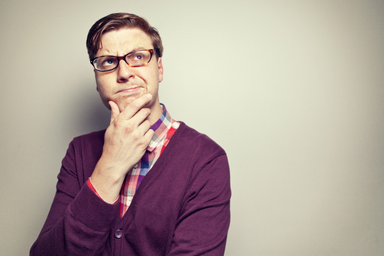 man wearing glasses and a purple sweater ponders the need for bone drafts with dental implants