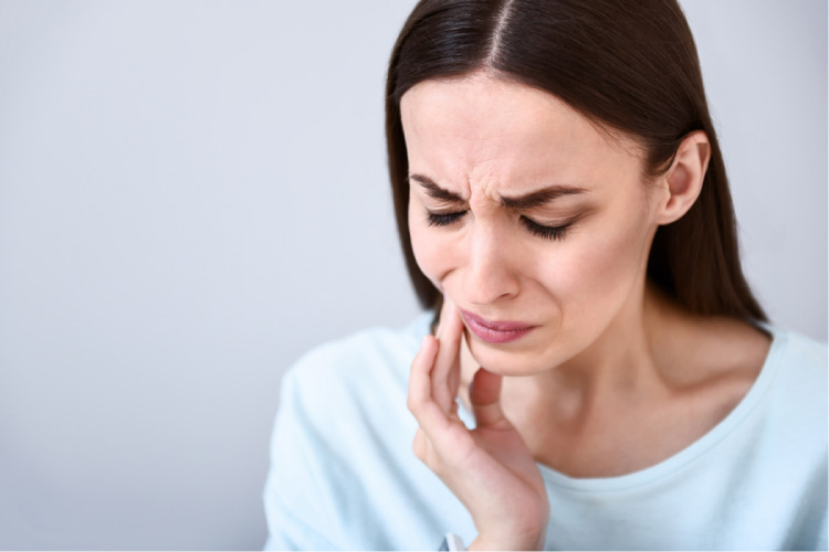 woman grimacing holding her mouth in pain with a cracked tooth