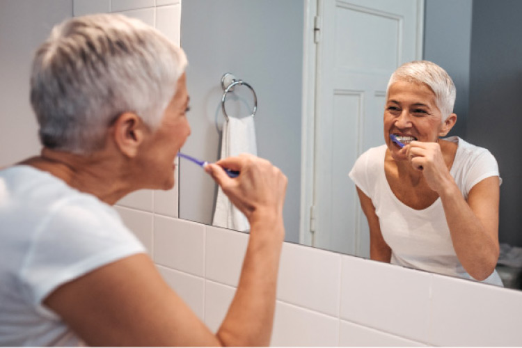older woman brushing her teeth in a mirror to preserve her restorative dentistry
