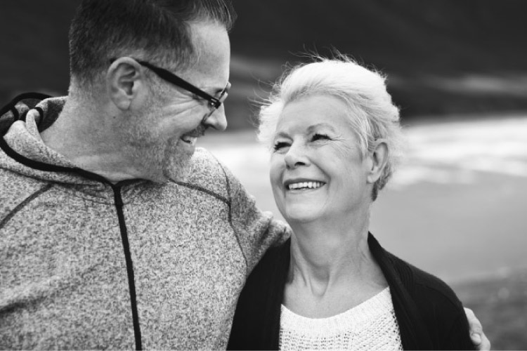 elderly couple look at each other and smile knowing they don't have gum disease