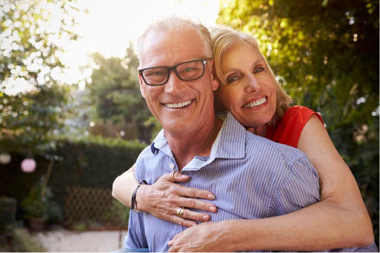 older couple hugging and smiling knowing they don't have periodontal disease