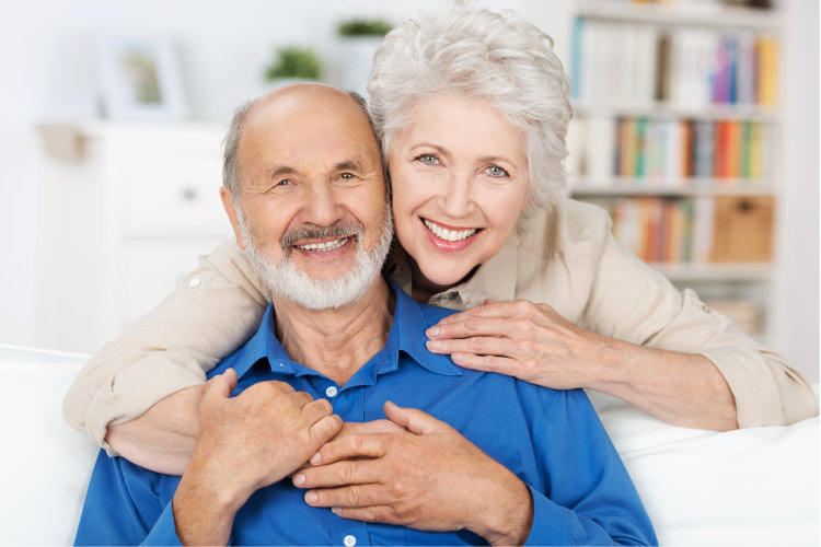 senior couple embrace and smile after learning about dental implants