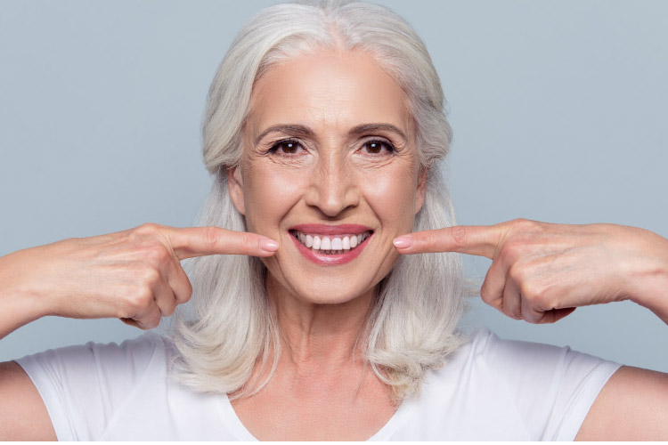white haired woman points to her straight white teeth with both fore fingers