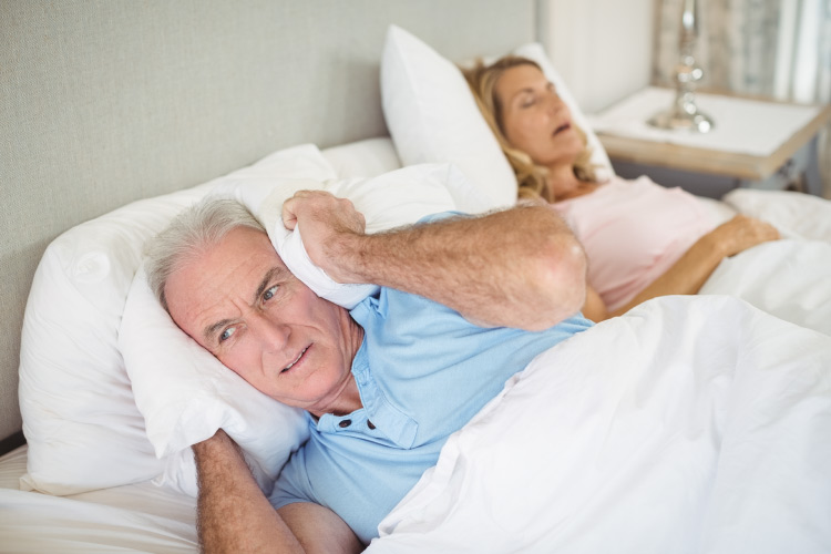 Older couple in bed with the woman snoring away and the man wide awake and covering his ears with a pillow