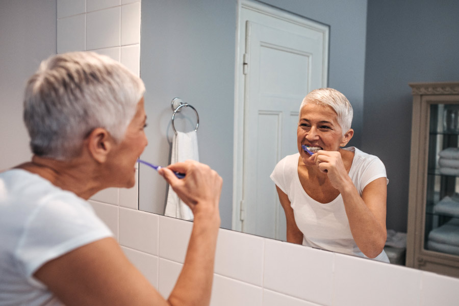 Lady with short gray hair brushing her teeth while looking in the mirror
