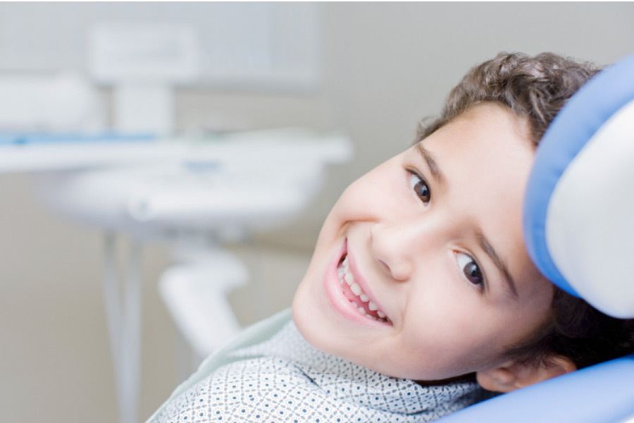 Smiling dark curly haired boy looking sideways from the dental chair