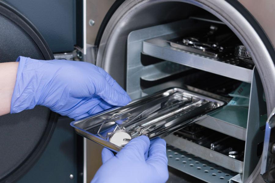 Gloved hands sterilizing equipment in a machine