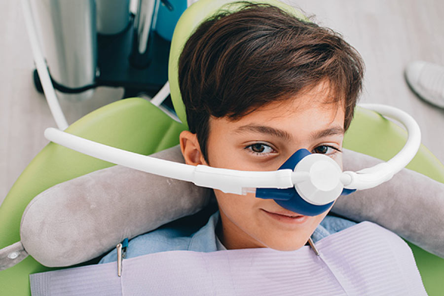 Brown haired boy in the dental chair with a nitrous oxide mask covering his nose ready for dental treatment