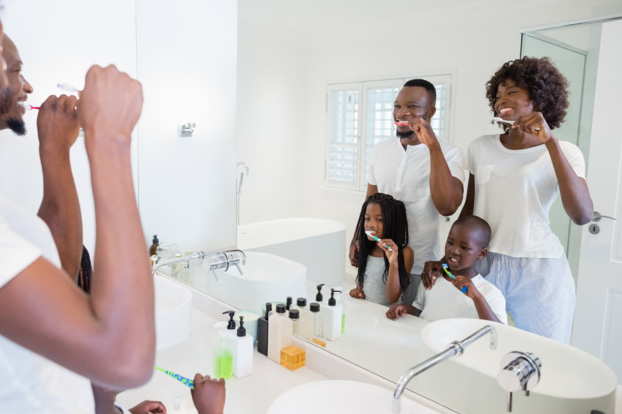 Black family including mom, dad and two kids brushing in front of the bathroom mirror