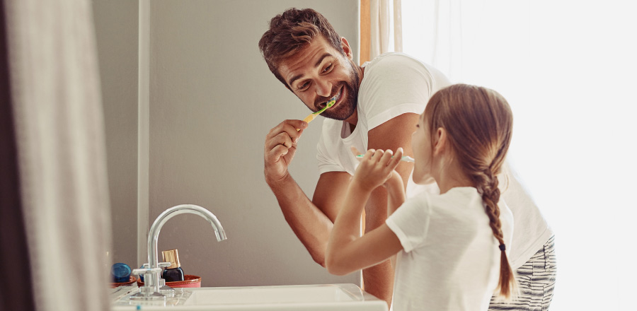 Side view of a dad & young daughter standing in front of the sink brushing their teeth