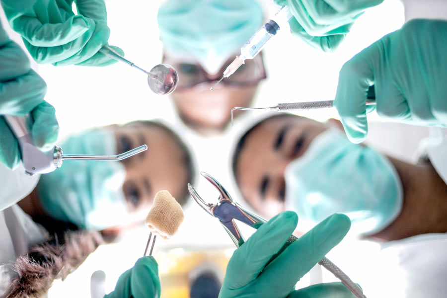 Masked dental professionals holding tools looking down on oral surgery patient