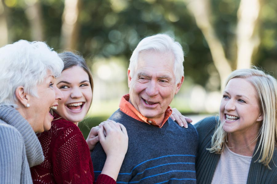 A senior couple laughing with their daughter and granddaughter outdoors