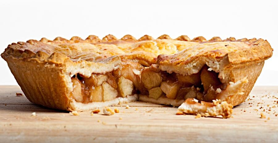 Side view of a delicious looking apple pie with one large piece removed