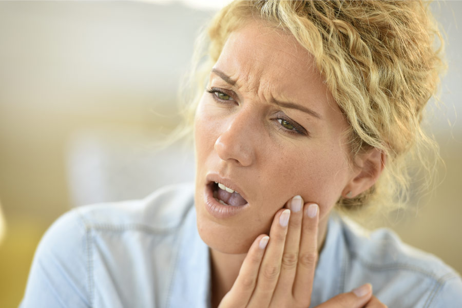 A blonde woman with curly hair has her hand to her jaw indicating tooth sensitivity.