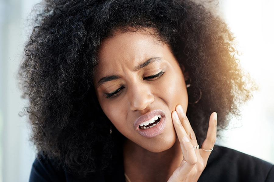 Attractive young woman with dark curly hair has her hand to her cheek and face looking pained due to a tooth infection.