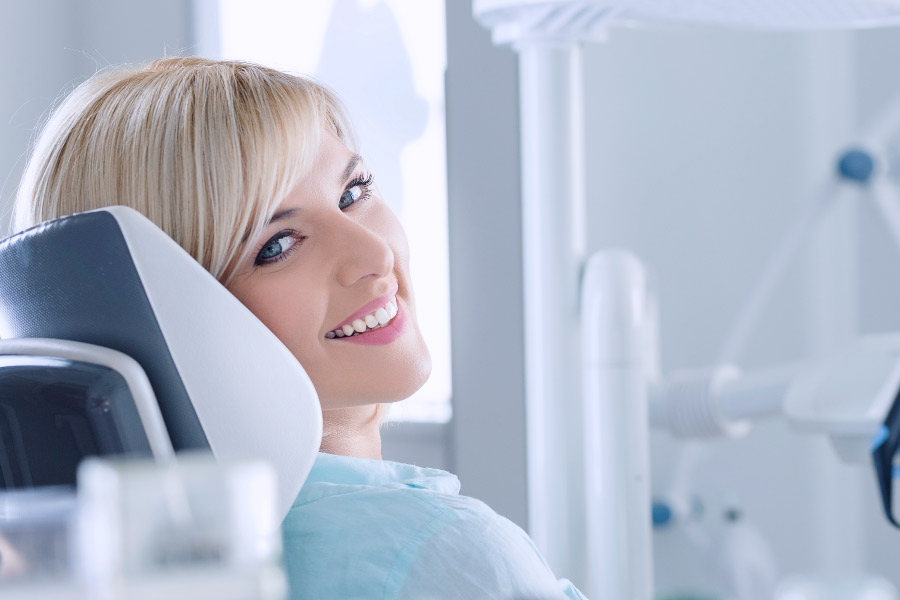 Smiling blonde woman with white teeth relaxing in the dental chair after teeth whitening treatment.
